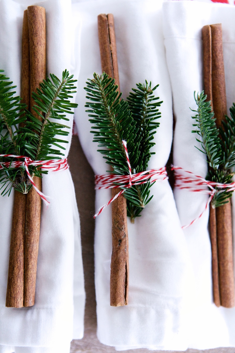 Napkins tied with cinnamon sticks, greenery and twine