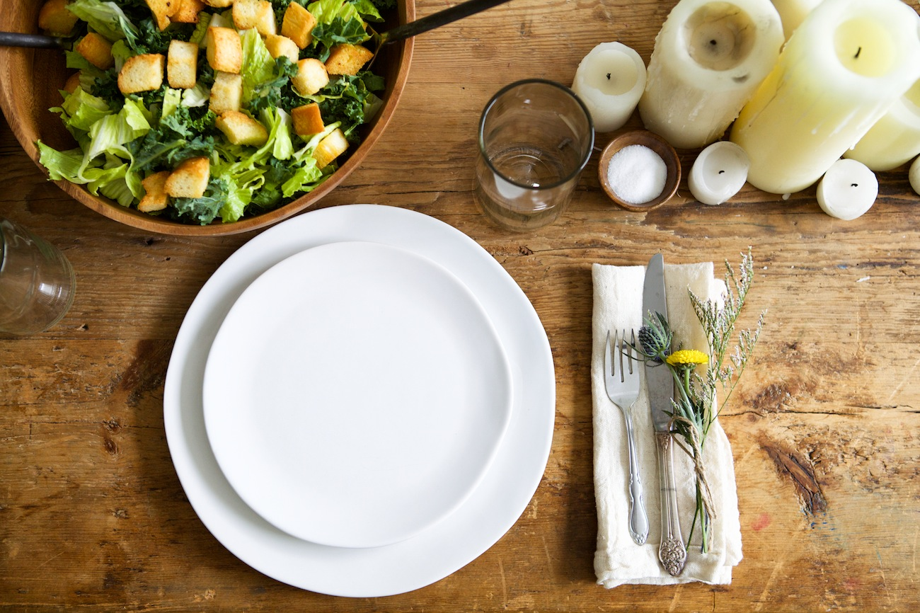 rustic spring natural tablesetting: salad, candles, white plates
