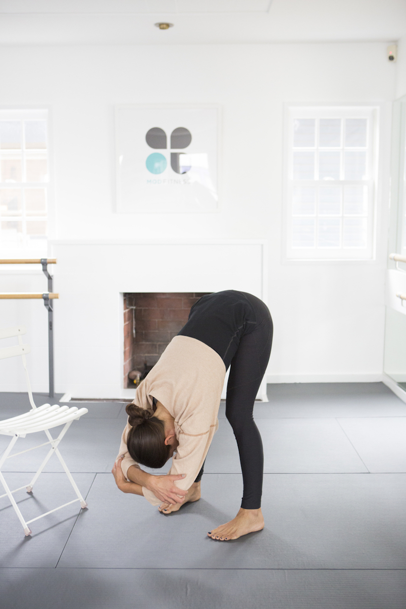 Standing forward bend holding elbows