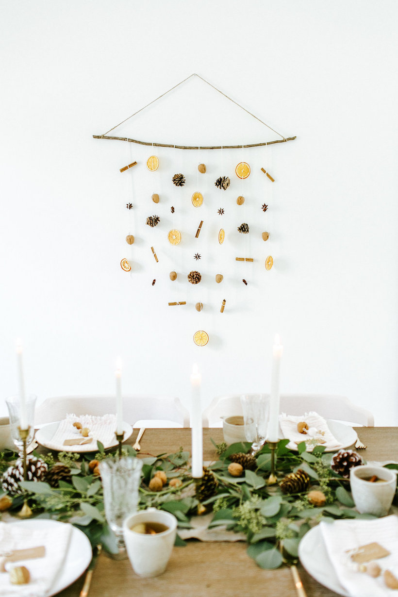 diy holiday wall hanging with dried oranges, walnuts, pinecones, cinnamon sticks, and star anise