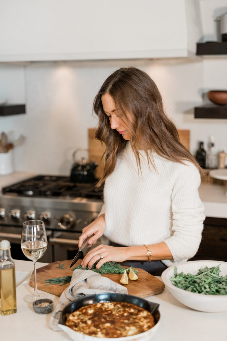 camille styles in kitchen making frittata