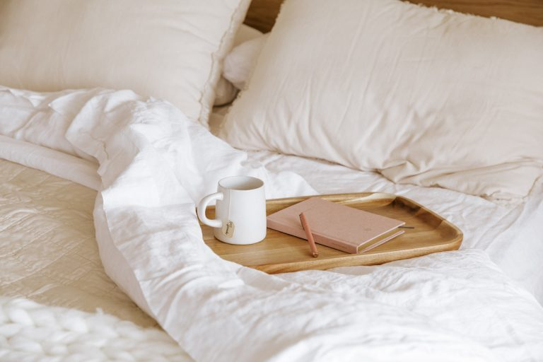journal and coffee in bed