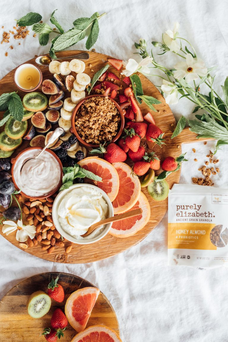 breakfast charcuterie board with fruit, yogurt, and granola