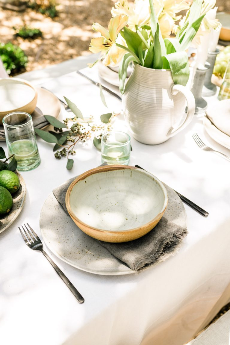 rustic place setting for a backyard dinner party with ceramic plates