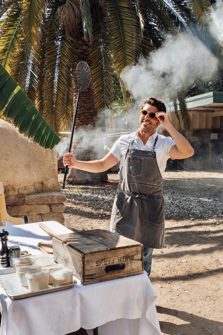 Oliver English making wood-fired pizza in an pizza oven at Plumcot Farm