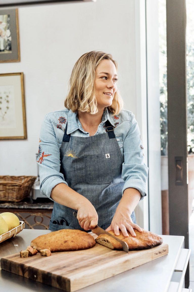 Alison Hersel cutting bread in kitchen, farmer at Plumcot Farm, Malibu